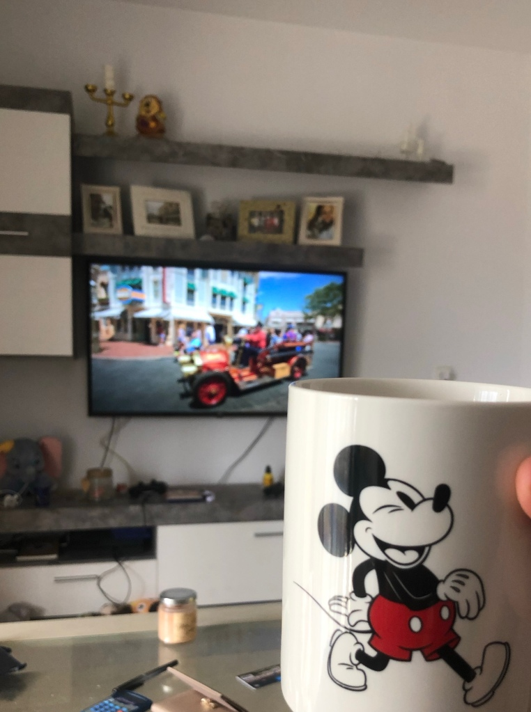 Drinking tea from Mickey mug watching the Imagineering story