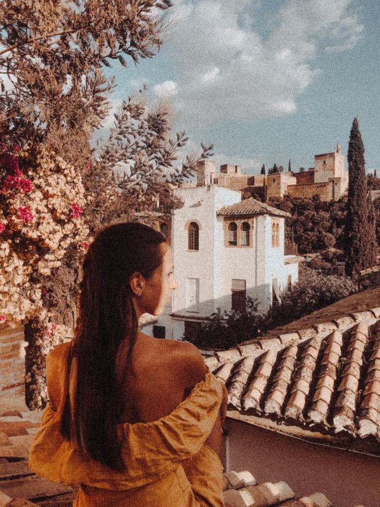 Vintage grainy effect Lauren wearing orange dress looking at Granada Alhambra