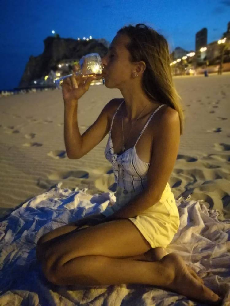 Girl drinking Croatian Wine on the Beach with a beautiful night sky behind