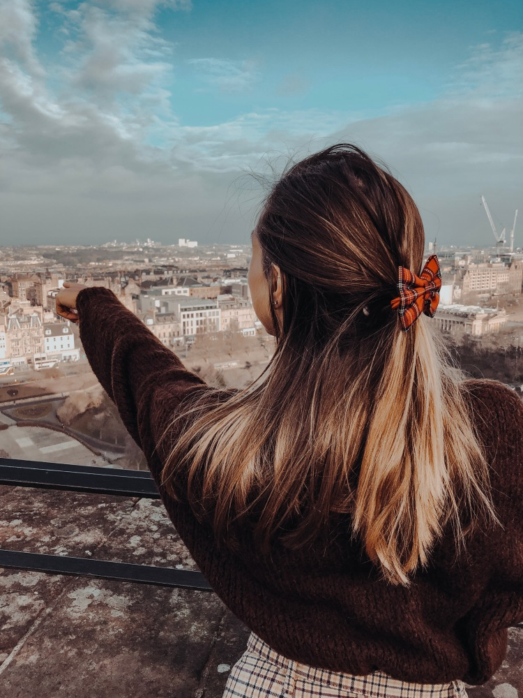 pointing to princes street from edinburgh castle girl wearing skirt jumper and tartan bow