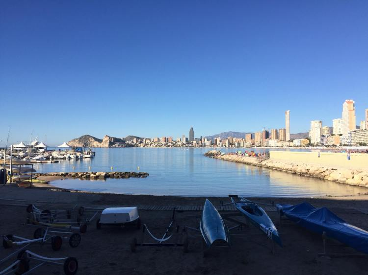 kayaks lined up at sports club at benidorm marina with benidorm and finestrat in the distance and the sea and high rise buildings