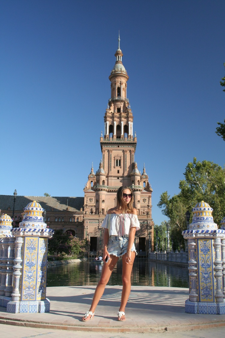 standing in front of the steeple of maria luisa park in plaza de espana