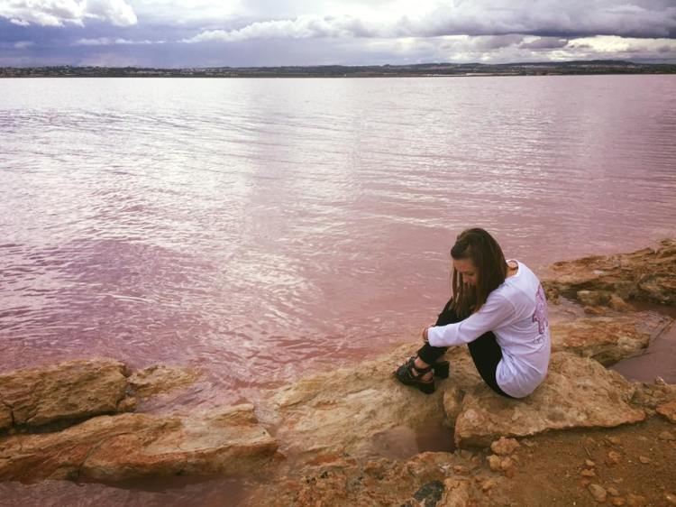 sitting on the pink water looking down at pink water and purple sky spain