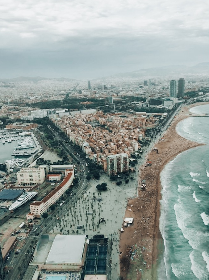 must visit cities airplane view of raining barcelona