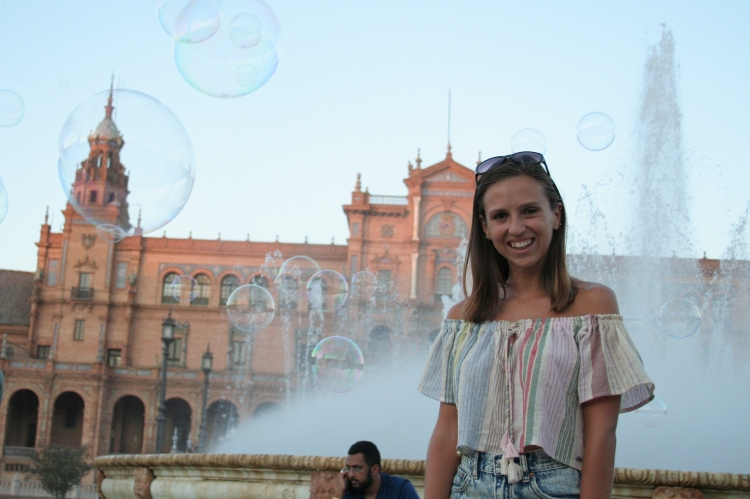 girl smiling with bubbles and fountain behind at maria luisa park plaza de espana
