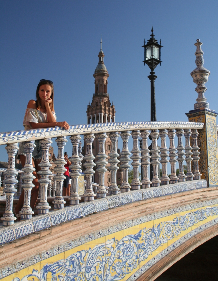 leaning smiling over the bridge in seville maria luisa park