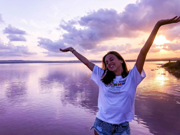 arms up smiling with pink water and sunset