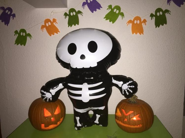 carved pumpkins with a skeleton inflatable and ghosts banner