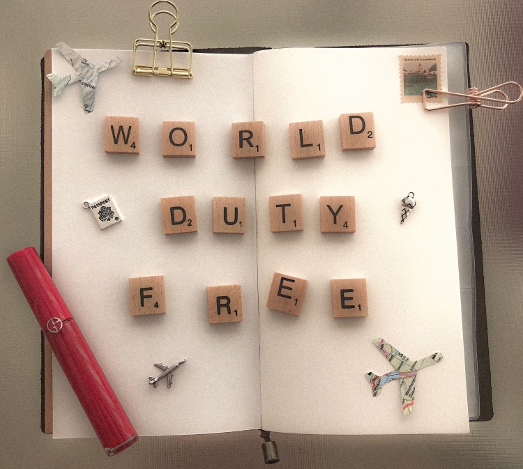 open nomad traveller book with the words world duty free with airplanes and giorgio armani lip colour