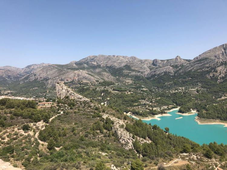 beautiful photo of the mountains and blue water at guadalest village near benidorm