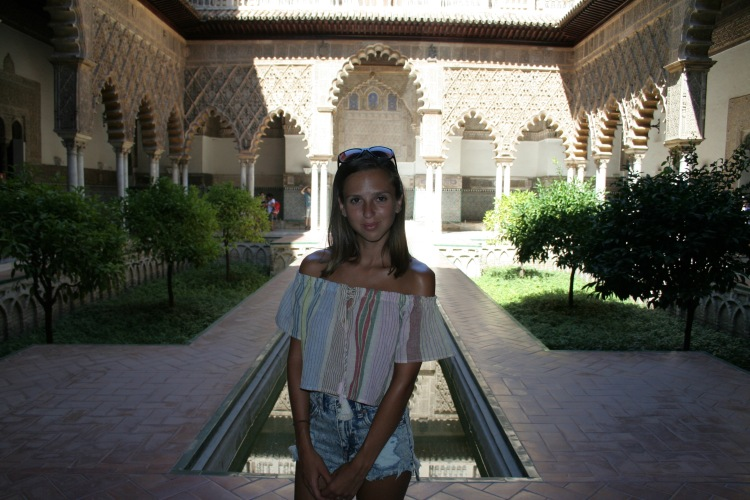 girl smiling with the sun reflecting behind in alcazar seville