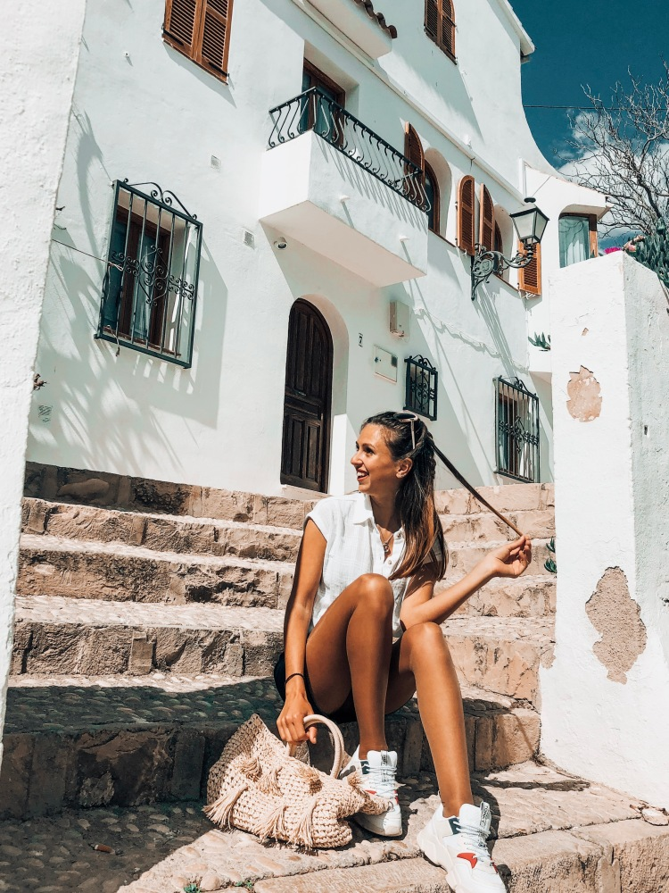 girl sitting on steps in altea with tommy hilfiger trainers