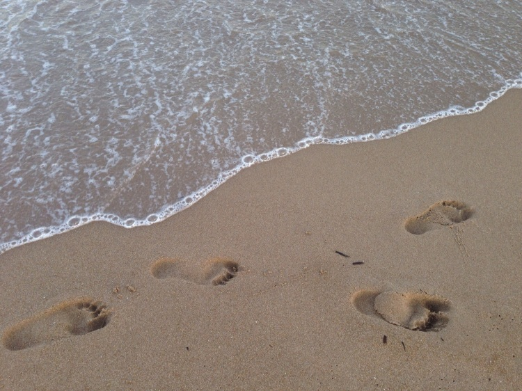 four footprints in the sand of levante beach with the shoreline
