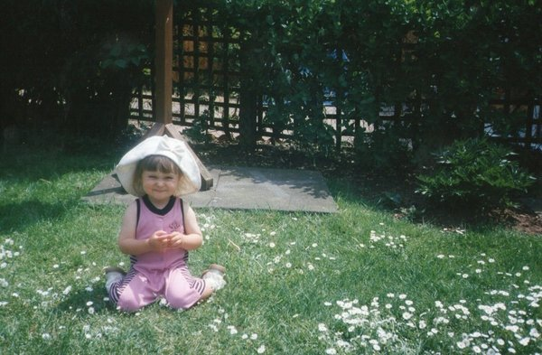 Sitting on the grass as a baby with pink tracksuit and white hat smiling
