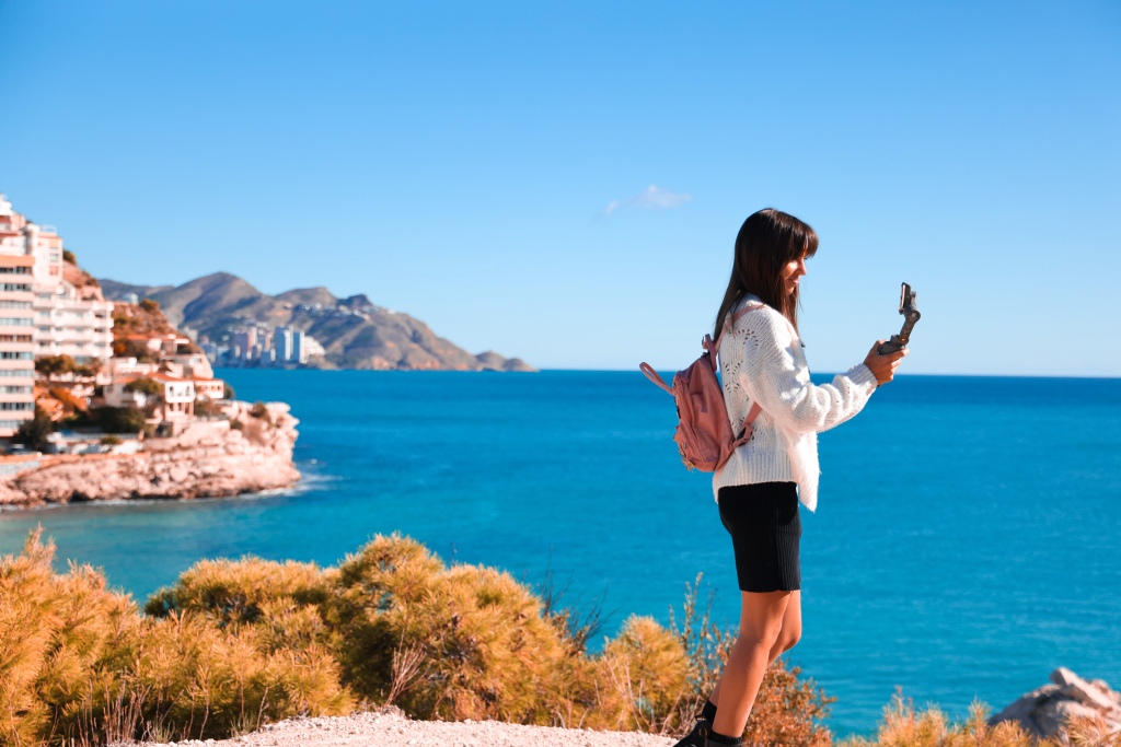 Girl holding iphone and gimbal  view of Finestrat and Benidorm behind