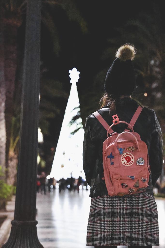 Girl standing facing Christmas tree back to camera